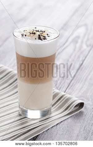 Sweet coffee with milk served in glass. Latte macchiato decorated with pinch of cacao and almonds flakes.