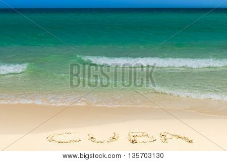Dream beach with waves and the name cuba written in the sand