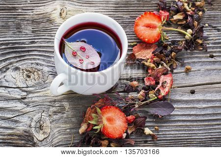Summer Fruit Tea. Easy fruit tea drink with barberry and fresh strawberries red berry color in a transparent cup on a simple wooden background. selective focus