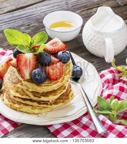Healthy homemade breakfast. Appetizing golden pancakes with strawberries, blueberries, honey, lime zest on a wooden background in rustic style