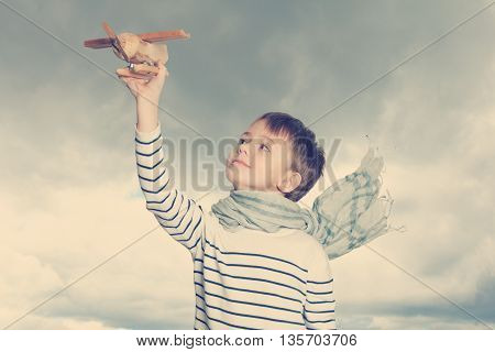 Carefree child with a airplane toy outdoors
