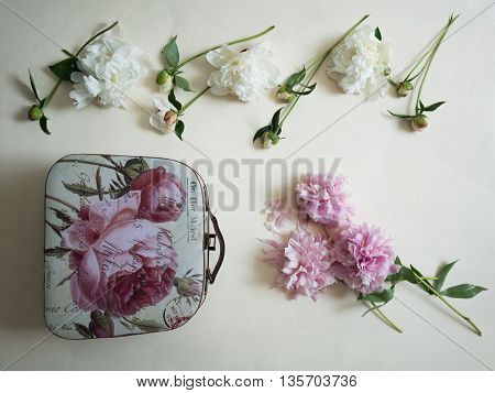 peonies with buds and womens handbags on the table. top view