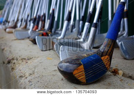 Row of many used old golf clubs lined up game sports