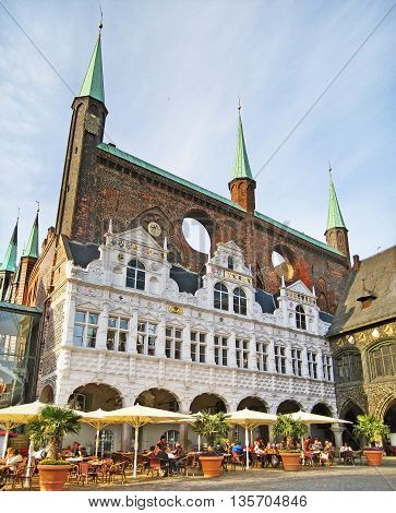 Luebeck Germany - May 23 2008: Town hall / historic brick building with people sitting in front in cafe / restaurant.