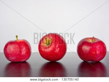 three apples on a black background with reflection