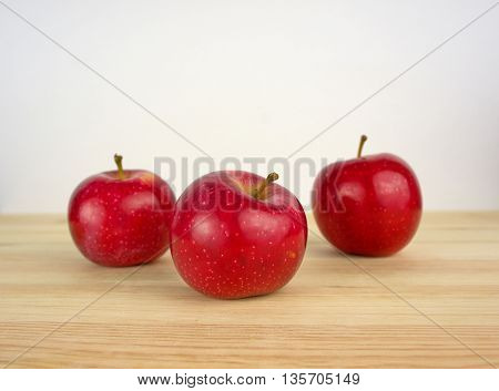 Three apples on a wooden background. Fresh harvest of apples.