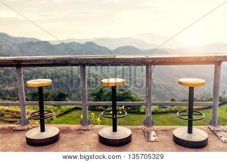Lonely empty chairs on a deck at sunrise ready for treveler to sit and relax. Travel and Relax concept.