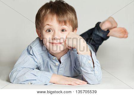 Cute child boy smyling on gray background