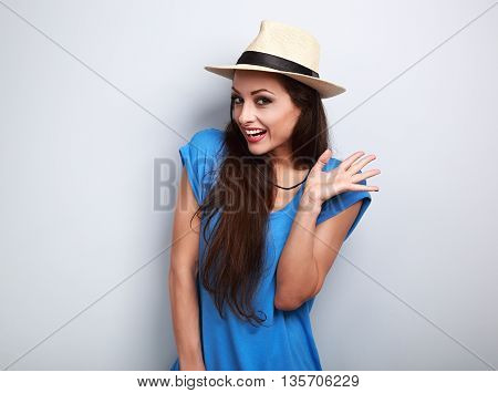 Happy Excited Young Woman In Blue Top And Summer Hat Looking On Blue Background