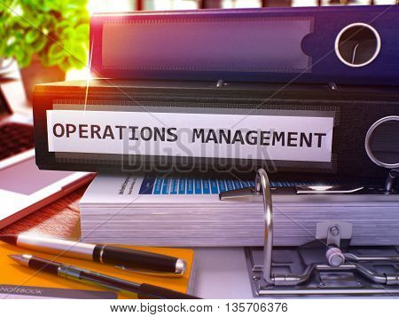 Black Ring Binder with Inscription Operations Management on Background of Working Table with Office Supplies and Laptop. Operations Management Business Concept on Blurred Background. 3D Render.