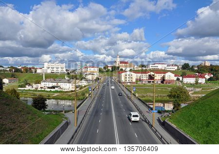 Grodno, Belarus - September 29, 2013: The historic panorama of Grodno. Road bridge in perspective. The Catholic church and the theater in the background.
