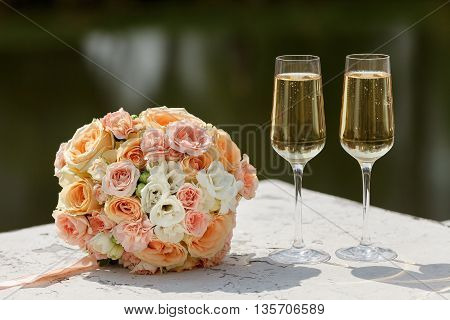 the bride's bouquet and two champagne glass.