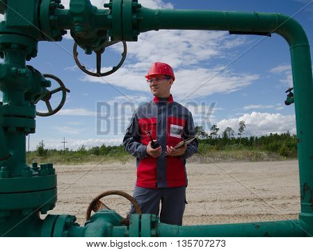 Worker near well head valve holding tablet computer and radio and wearing red helmet in the oilfield. Oil and gas concept.