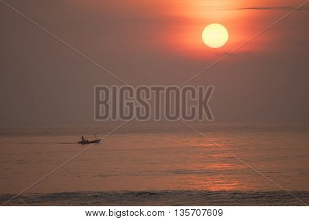 Summer beach coast landscape at sunset with fishing boat in the horizon fisherman silhouette on ocean water.