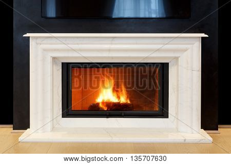 classic white marble fireplace with burning fire in it