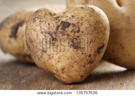 heart shaped potatoes on oak table, shallow focus
