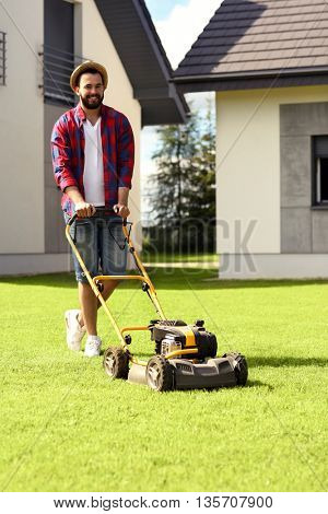 Picture of a young man mowing the lawn