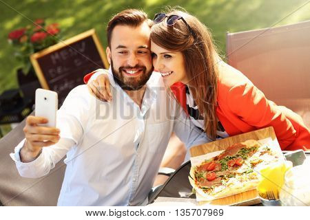 Picture of young couple taking selfie in a restaurant