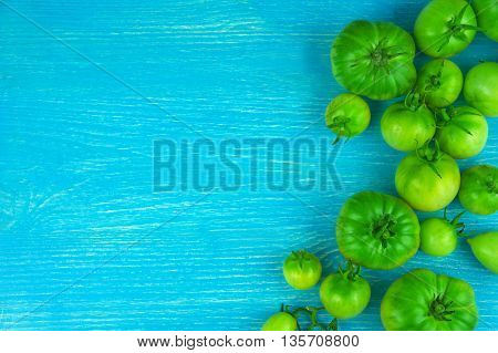 green tomatoes on a blue wooden background