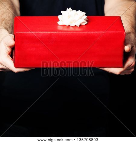 Gift Box and Male Hands on Black Background