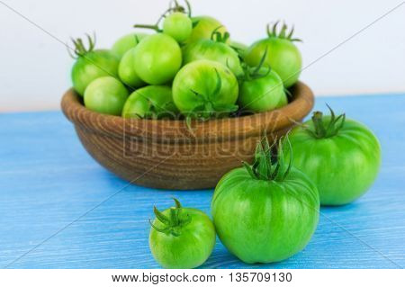 green tomatoes in a wooden bowl. Green tomatoes on blue table.