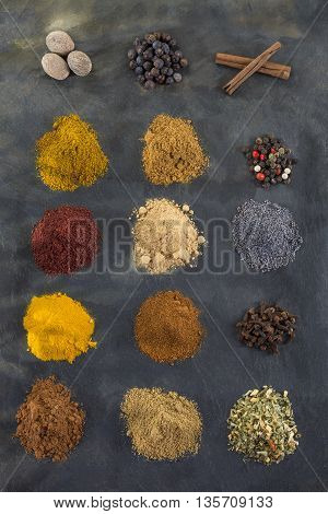 Selection of various bay and spice powder on slate background