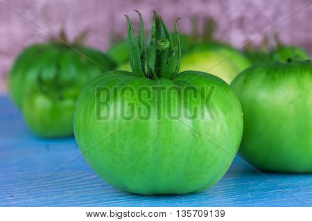 Green tomatoes on blue table. Juicy vegetables.