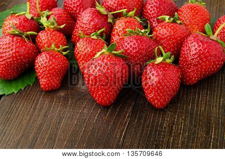 strawberries on old wooden background front view