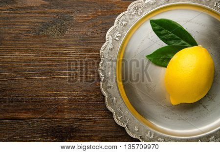 lemon with leaves on a vintage plate top view