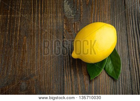 lemon with leaves on a wooden backgrond