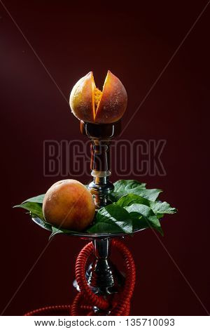 Smoking hookah with fruit head on dark background