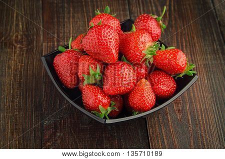 Strawberries with leaves in black plate. wooden background.