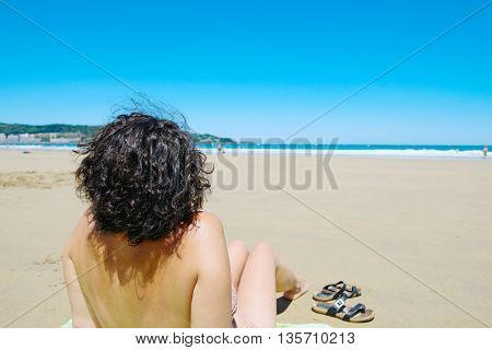 a middle aged woman resting at beach near the sea