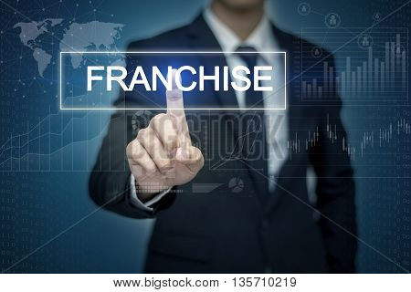 Businessman hand touching FRANCHISE button on virtual screen