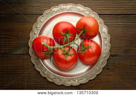 Fresh tomatoes on a vintage plate top view