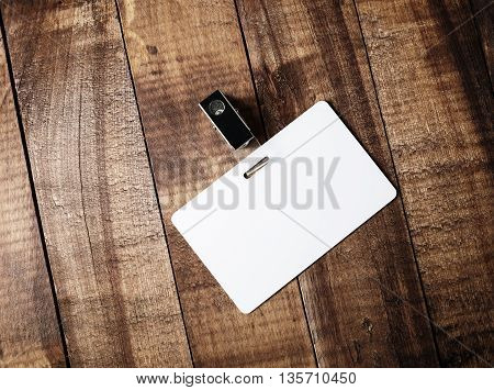Blank white plastic badge on vintage wooden table background. Responsive design template. Blank template for for ID. Mock-up for your design. Top view.