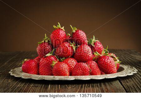 fresh tasty strawberries on vitage plate, wooden background