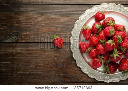 strawberries on vitage plate, wooden background top view