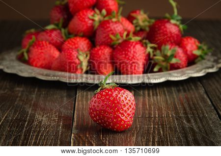 strawberries on vitage plate, wooden background front view