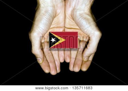 Flag Of East Timor In Hands On Black Background