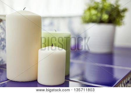 Three candles on windowsill in bathroom blured