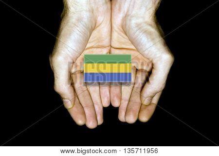 Flag Of Gabon In Hands On Black Background