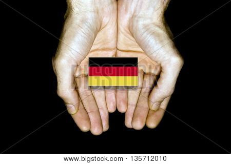 Flag Of Germany In Hands On Black Background