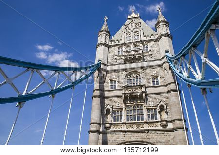 Looking up at one of the towers of Tower Bridge which spans over the River Thames in London.