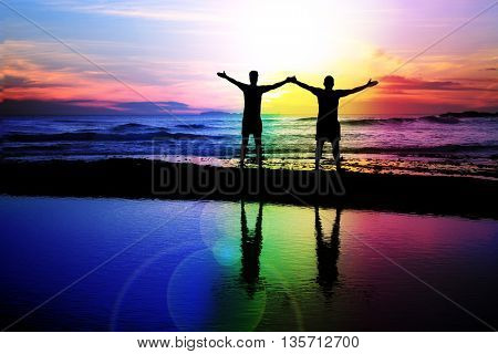Silhouette of a gay couple on the beach with a rainbow sunset.