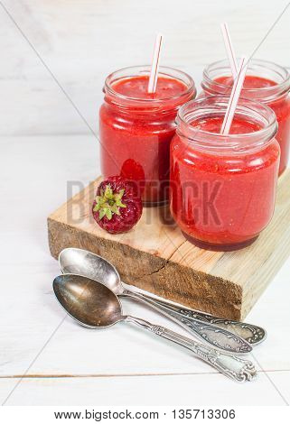 Fresh strawberry in a glass with a straw. On a white wooden surface.