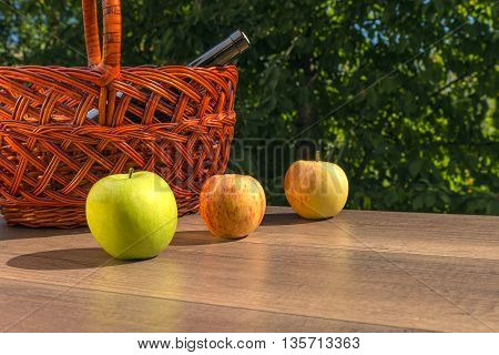 colored apples on the table on the background basket with wine