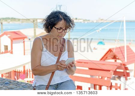 a middle-aged woman with a phone on the beach