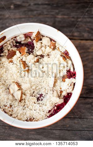 Cherry, rhubarb and strawberry crumble on a wooden background
