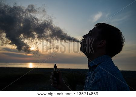 A man smoking vaping e-cigarette vape box mode over golden sunset.